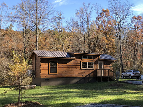 Park Model Log Cabin with a brown metal roof - Tiny Log Cabins at Acony Bell Tiny Home Village - Open House at Acony Bell Tiny Home Village – Project Small House