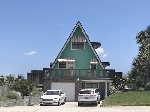 The little A-Frame beach house has a garage under it.