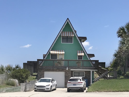 The little A-Frame beach house has a garage under it.