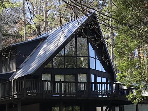 A-Frame with Bump-out Shed Roof Addition - The whole front of the house is glass, upstairs and downstairs.