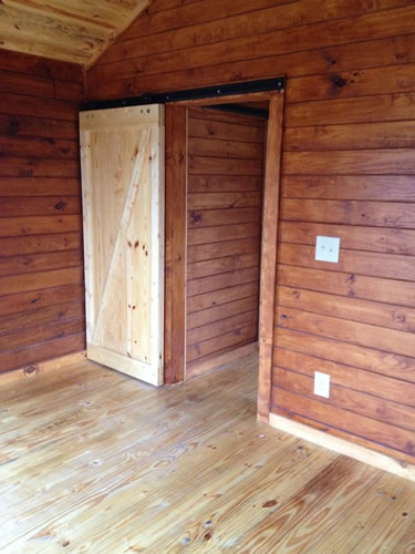 Interior with sliding barn door and tongue and groove wood walls