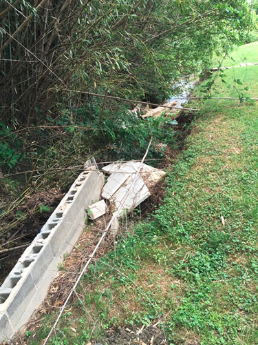 When the first part of the retaining wall collapsed, it blocked the water, so it began to cut under more of the wall, which then collapsed.