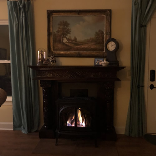 The mantel on, fire going, with the wall painted dark grey inside the mantel