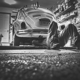 A person fixing underneath a bug car in a shop