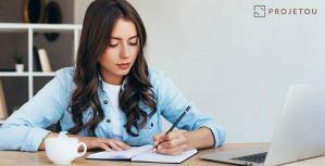 Aluna de arquitetura fazendo curso online em computador branco enquanto escreve de lápis em um caderno e toma café