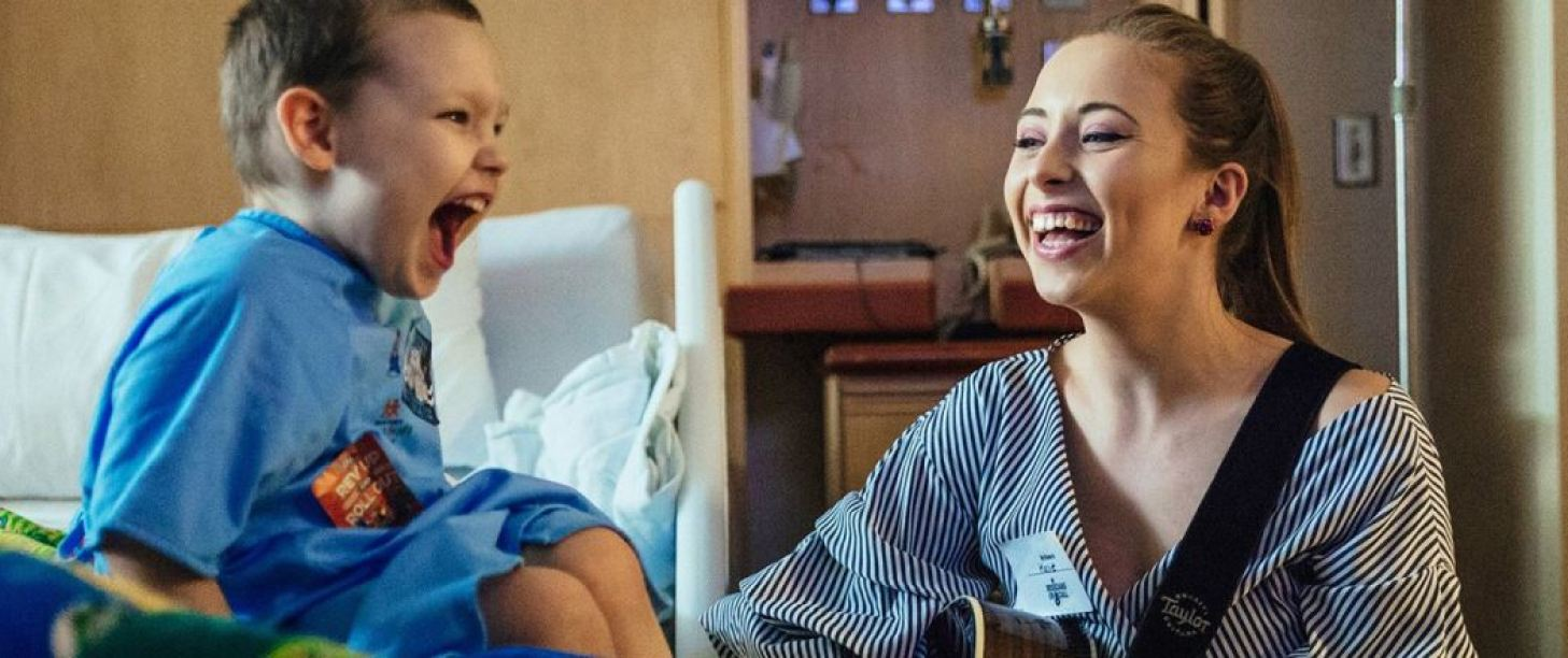Give a little bit of love to Musicians on call excited young boy in hospital with laughing musician