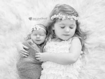 Black and white image of big and little sis with flower crowns and their eyes closed.