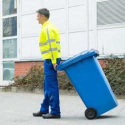 Valet Trash Worker Hauling Trash Can For A Brief Overview of Valet Trash Services Blog