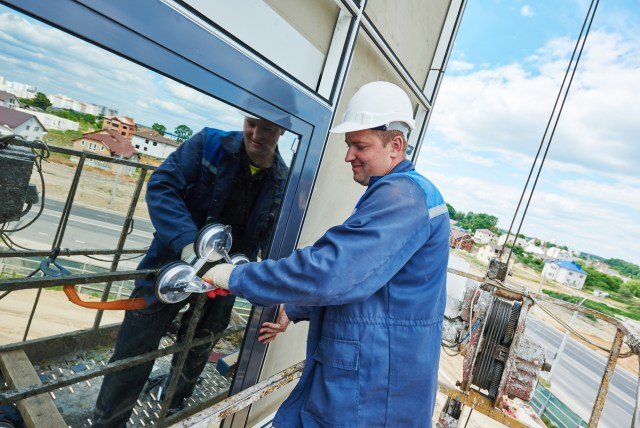 Worker Replacing Commercial Window For What Are CapEx Projects Blog