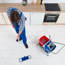 Man Cleaning Kitchen Floor In Rental Property For How To Clean Residential Rental Property Blog On Property Manager Insider