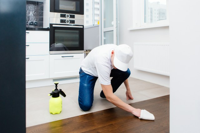 Man Wiping Down Wood Floor By Hand In Rental Property For How To Clean Residential Rental Property Blog On Property Manager Insider