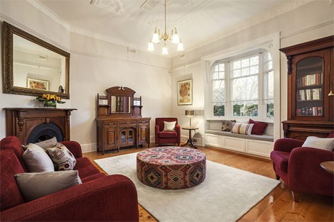 Original fireplace and ceiling complement the bay window kept as a window seat