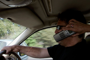 South African Daniel Brink, who was working as a guard in Iraq when his SUV was hit by roadside bombs, uses a phone held by his wife in Pretoria. (Francine Orr/Los Angeles Times)