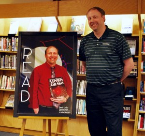 """David Leake, Planetarium Director and Professor of Natural Sciences, poses next to a poster promoting his book, """"Cosmos,"""" which was Parkland Library's annual READ Poster in celebration of Nation Library week, which took place April 12-18, 2015."""