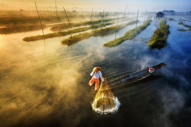 Πρώτο βραβείο, κατηγορία Τοπίο (Επαγγελματίες). Ψαράς της εθνοτικής ομάδας Intha ρίχνει τα δίχτυα για ψάρεμα, ενώ παράλληλα κωπηλατεί με έναν μοναδικό τρόπο -χρησιμοποιώντας το πόδι του- στη λίμνη Ινλε της Μιανμάρ