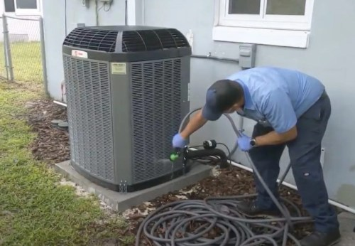 man cleaning the condenser coil