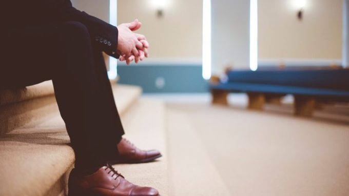 man leans over in prayer inside a church sanctuary