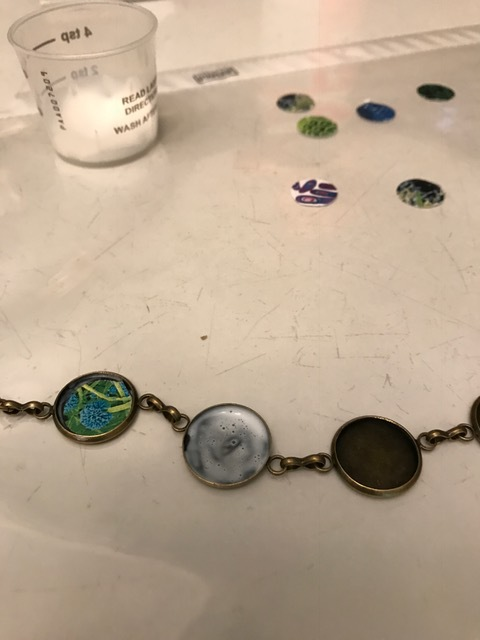 using mod lodge to seal pictures in jewelry bezel before adding resin