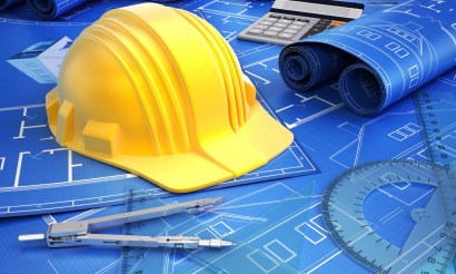 A picture of tools used in architecture including a hard hat, compas and blueprint