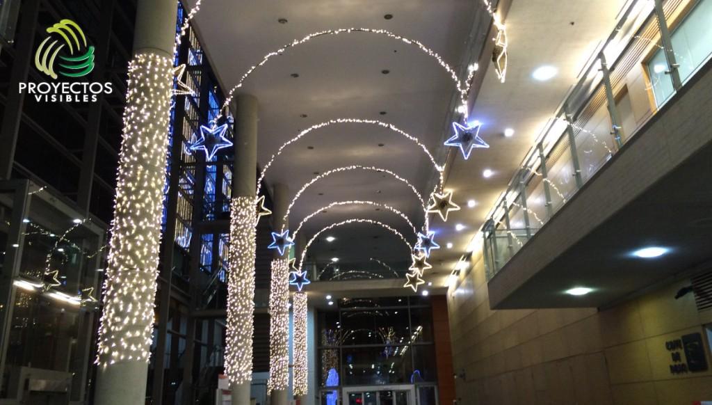 Decoración navideña con cortinas en las columnas y arcos con estrellas led