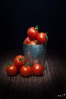 pomidory koktajlowe w srebrnej szklance na brązowaych deskach