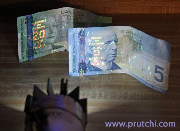 diy high-power 365nm flashlight showing fluorescence of Canadian bills www.prutchi.com www.diyPhysics.com