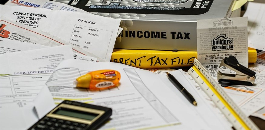 Income Tax books, papers and calculator on the table