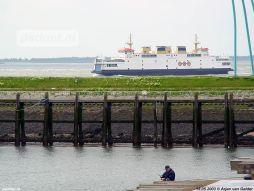 Een visser met de veerboot op de achtergrond