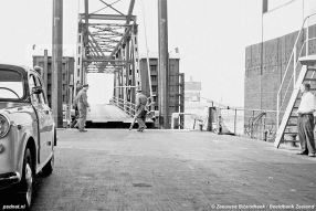 Bij vertrek spant de bemanning (links in beeld) een ketting bij het ontbreken van een echte deur op de Krammer en Zijpe.