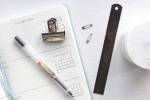 a Calendar book with a pen, clippy, and ruler