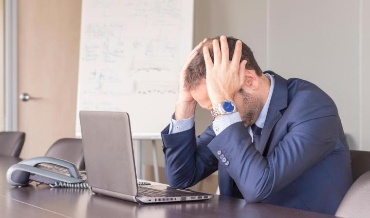 Hombre en el trabajo padeciendo de ansiedad, ya que no consigue concentrarse para terminar su trabajo