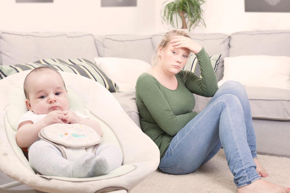 Madre sufriendo depresión post-parto al lado de se hijo