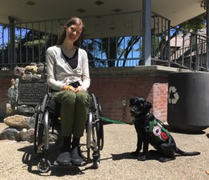Chanda smiles from her wheelchair out in the sun at a park with Kestrel, a black lab puppy in a vest