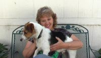 Margie Cantwell smiles and sits with Jack (a Jack Russell Terrier) in her lap