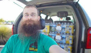 Brad takes a selfie in a green PSDP t-shirt with a trunkful of water donations in the background.