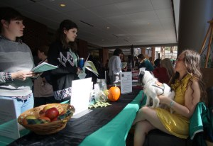 Veronica interacts with students from behind a full PSDP exhibition table at Winthrop's Accessibility Awareness Fair