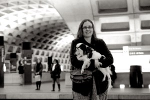 (Black and white photo) Veronica smiles in a DC Metro subway station underground, holding Hestia, a small white dog with black patches