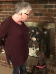 In front of a brick fireplace with a snowman decoration, a Chocolate Labrador Retriever looks up to the left at a talking woman with short gray hair and black-rimmed glasses in a burgundy sweater.