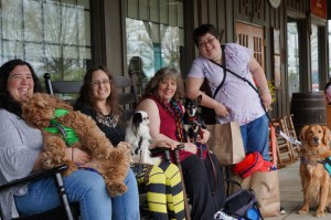 Four service dog users joyfully smile at the camera as they sit on rocking chairs outside of a Cracker Barrel restaurant.