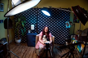A smiling white woman sits with a small white and black dog in her lap, in a room where she is surrounded by lighting and filming equipment.