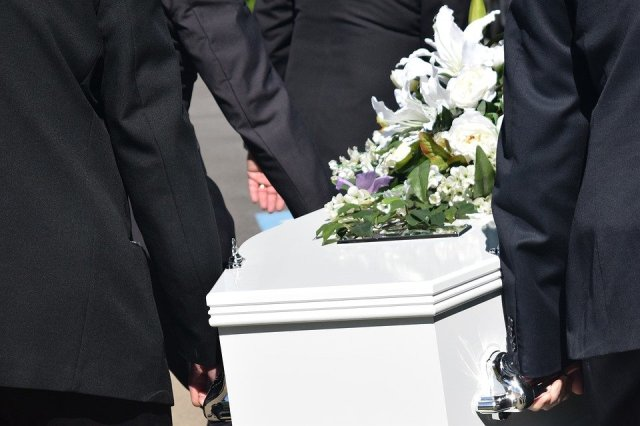 men carrying a coffin at a funeral