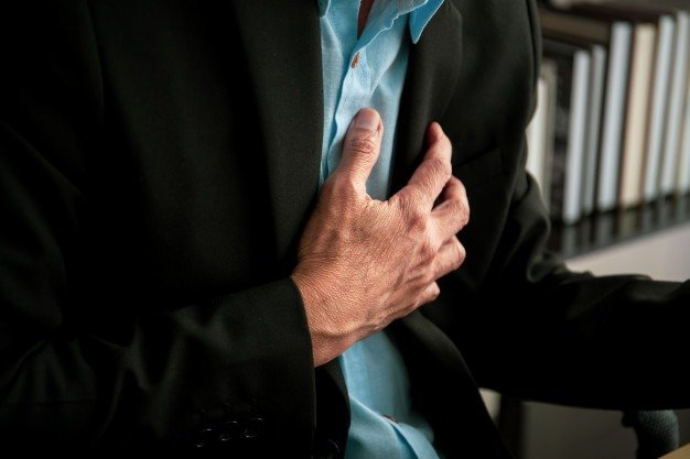 man holding his chest because of pain