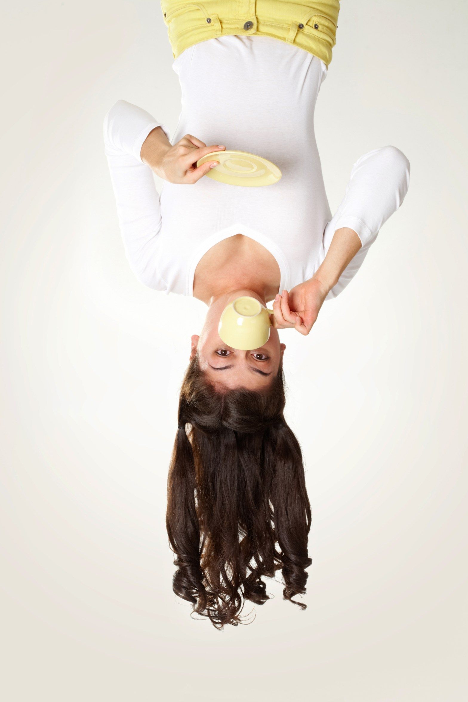 Woman hanging upside down and driking from a cup to cure hiccups