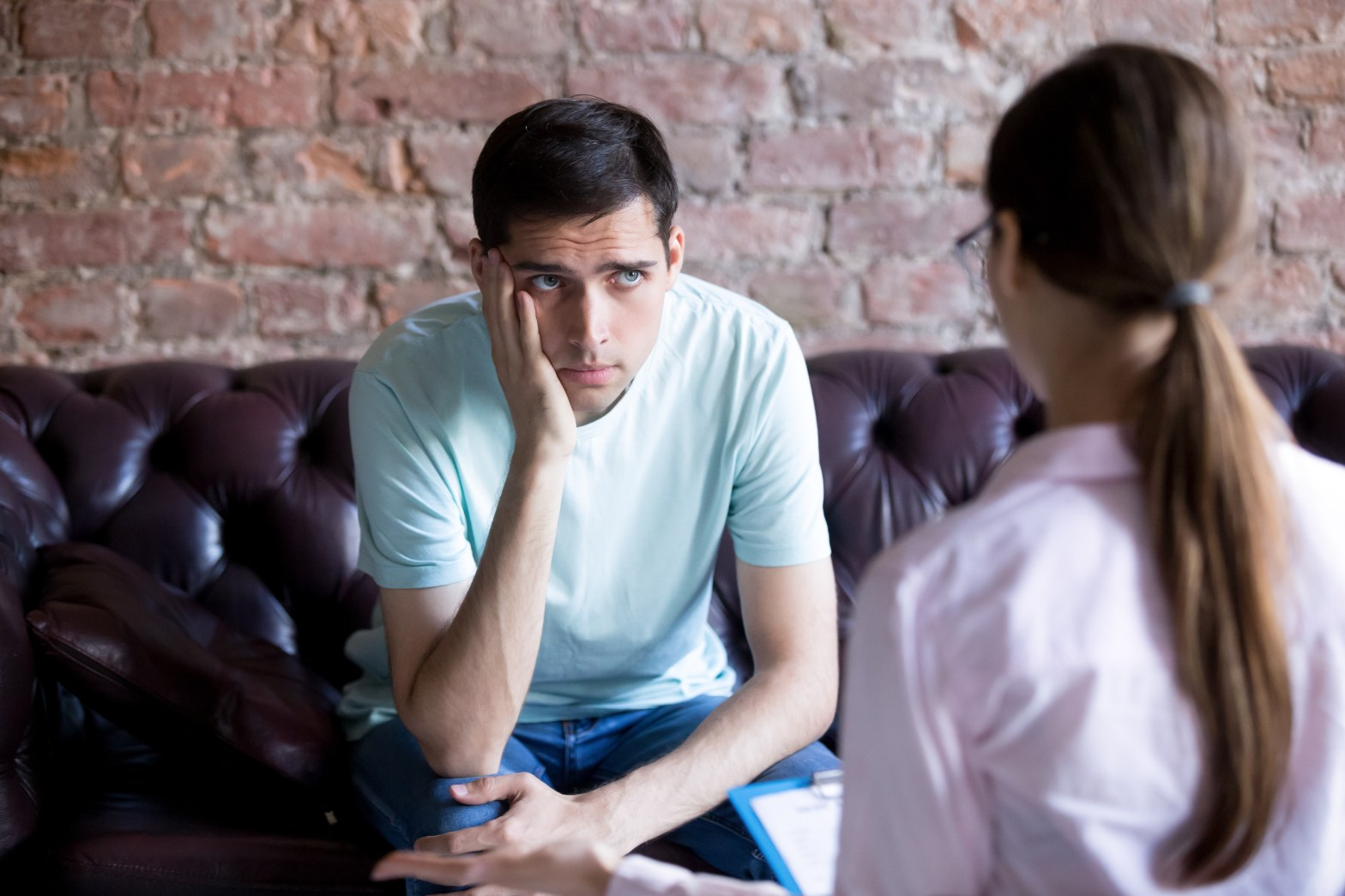 Unhappy male coachee listening to an executive coach give advice. Frustrated client holding a hand to his face.