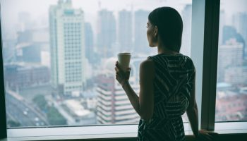 Businesswoman drinking coffee at work contemplative looking out the window of high rise skyscraper building during morning tea break. Workplace stress, mental health in the workplace.