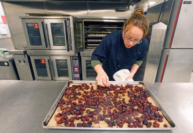 """Stacey Larsen, Port Townsend School District's director of food service, checks on a tray of roasted beets Tuesday morning, Nov. 24, ahead of that day's Thanksgiving feast lunch. The beets, which came from Dharma Ridge Farm in Chimacum, were originally intended for teachers and staff only, but Larsen made too many and decided the students might like some, too. """"They're like candy,"""" she said upon tasting one. """"I think the kids will like these as much as the teachers."""" Photo by Nicholas Johnson"""