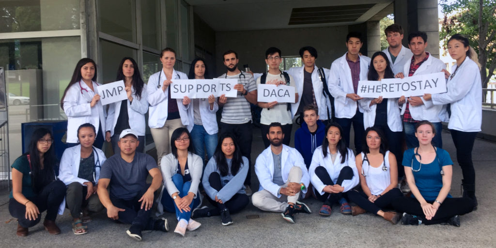 Student in lab coats hold handwritten signs outside of building.