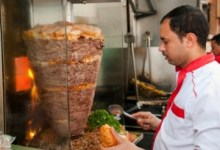 Fast food shop employee preparing kebab sandwich