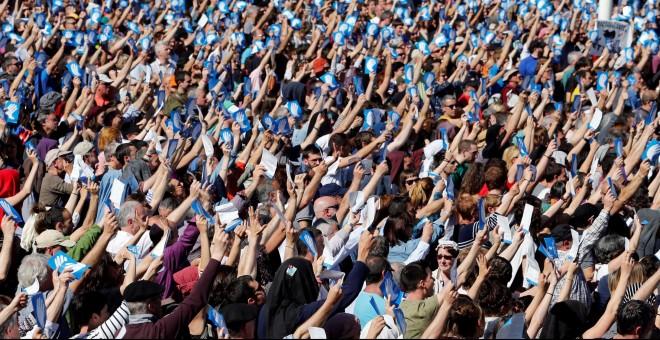 Una multitud de personas sostienen el símbolo de los llamados Artesanos de la Paz, los organizadores del desarme de ETA, en la concentración de Baiona. REUTERS / Regis Duvignau