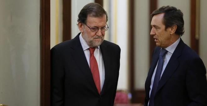 El presidente del Gobierno, Mariano Rajoy (i), conversa con el portavoz del PP en el Congreso, Rafael Hernando, en los pasillos de la Cámara Baja. /EFE